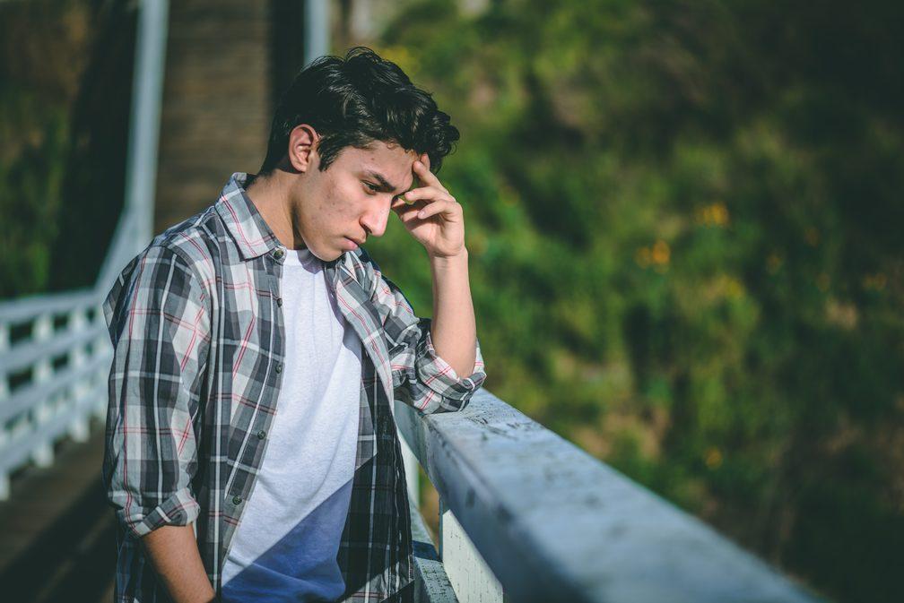 depressed man looking over an overlook