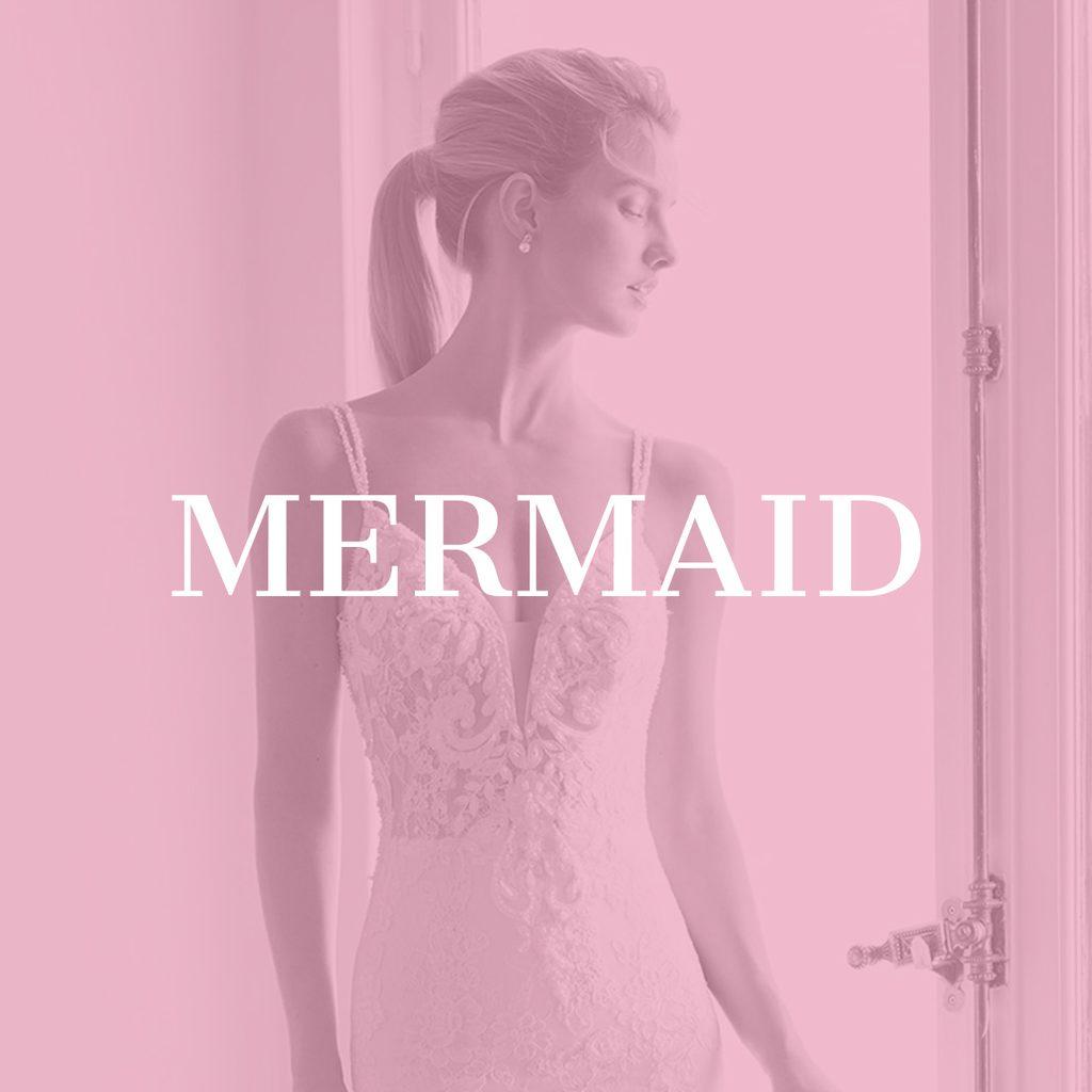 Braut in figurbetonten Mermaid Brautkleid mit Spitze am Fenster stehend