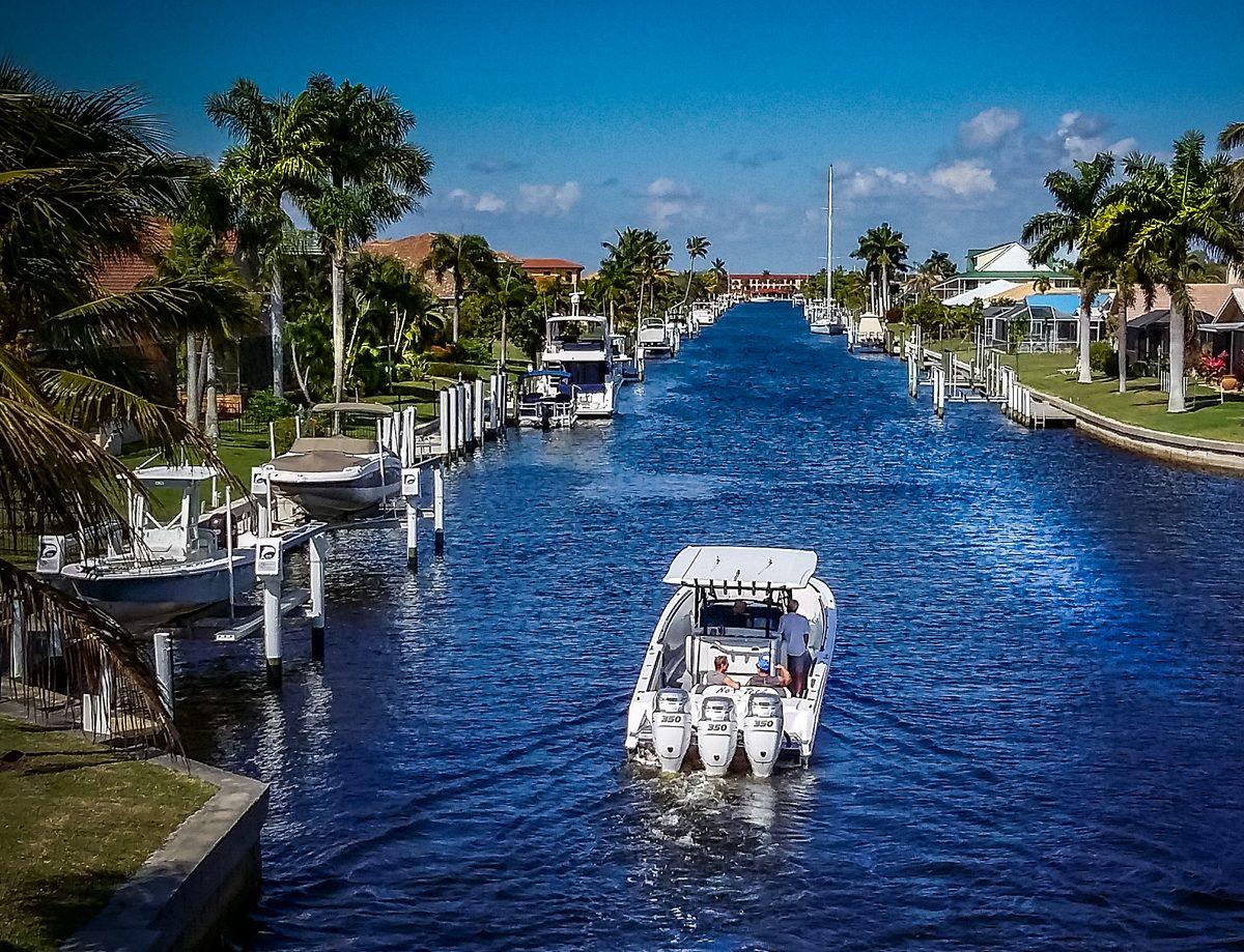 Ein Motorboot mit drei Außenborder-Motoren zu sehen ist, dass in einem Frischwasserkanal im Rotonda Circle langsam entlang fährt.