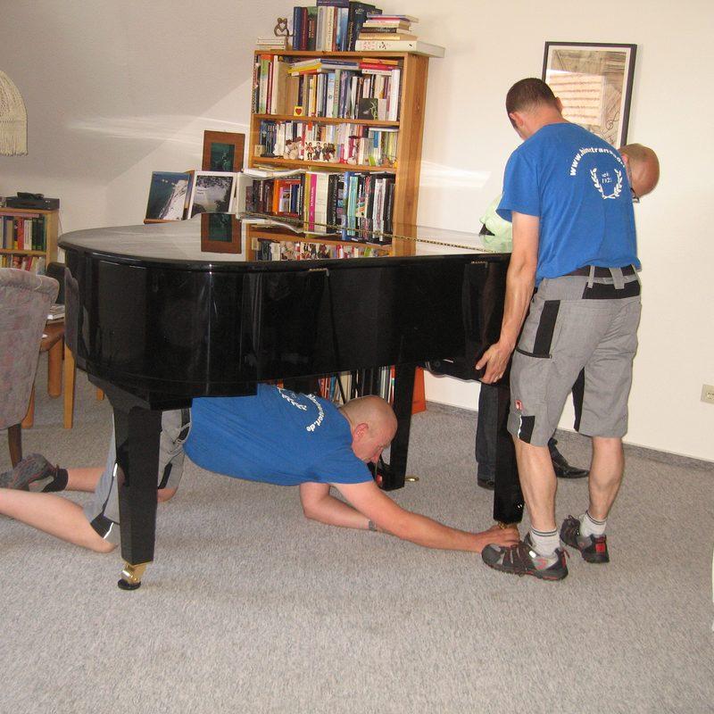 Ein Klavier wird durch die Mitarbeiter der Paul Hinz Transport GmbH transportfähig gemacht.